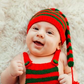 Menino encantador em longo chapéu verde e vermelho está no tapete esponjoso