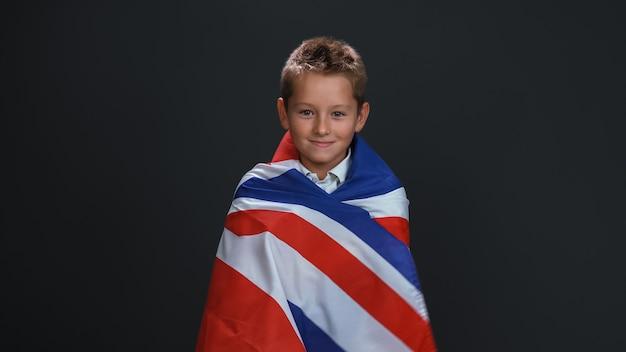 Menino encantador envolto em uma bandeira do reino unido celebra o dia da independência e expressa patriotismo isolado na parede preta
