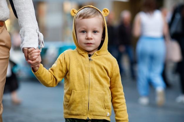 Menino encantador na jaqueta amarela detém a mão da mãe