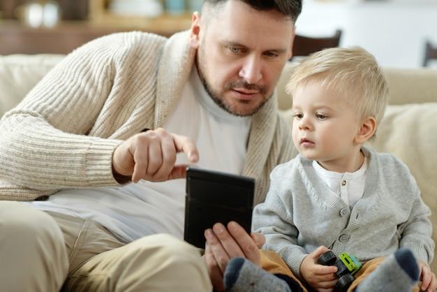 Menino encantador olhando curiosamente para o gadget portátil nas mãos do pai sentado no sofá