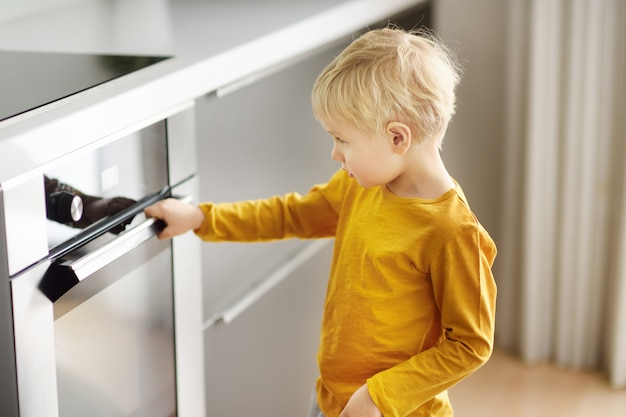 Menino encantador que espera preparando o alimento na cozinha doméstica.