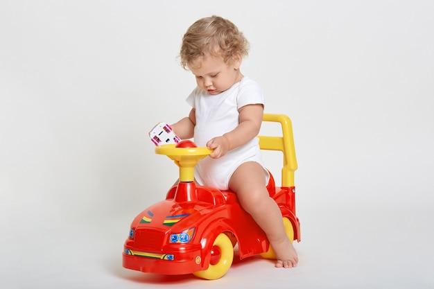 Menino encantador sentado em um tolocar vermelho e amarelo, segurando um carrinho de brinquedo nas mãos, vestindo um macacão branco