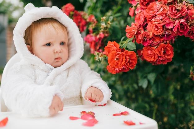 Menino encantador, sentado na cadeira alta ao ar livre nos arbustos com flores