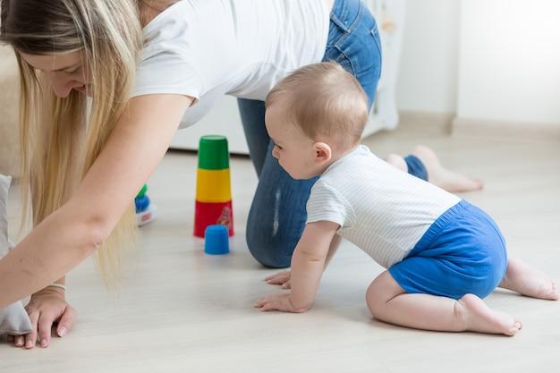 Menino engatinhando no chão e montando uma torre de brinquedo com a mãe
