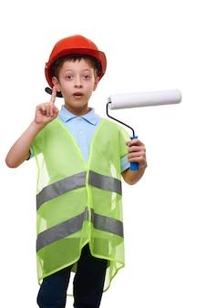 Menino, engenheiro, construtor, pintor em capacete de segurança de construção, segura o rolo de pintura e mostra o gesto do dedo