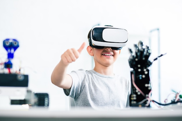 Menino engenhoso positivo sentado à mesa enquanto testa sua mão robótica humanóide com a ajuda de tecnologias de realidade virtual