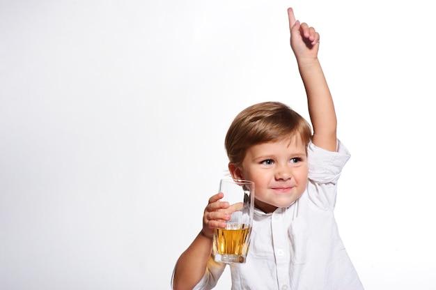 Menino engraçado, bebendo um suco fresco