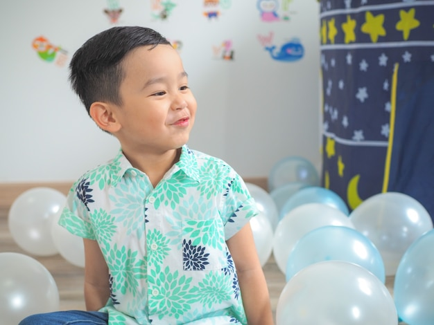 Menino engraçado brincar com balões coloridos