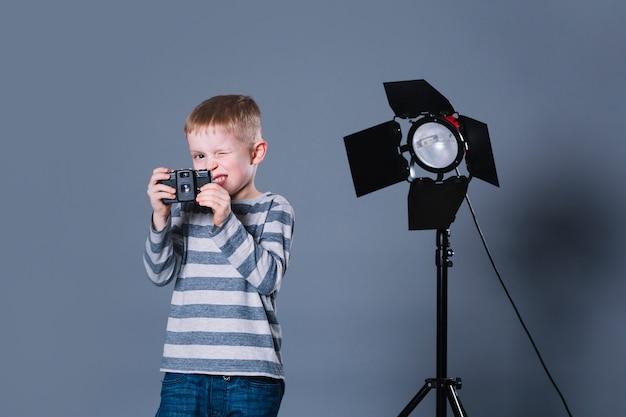 Menino engraçado com câmera