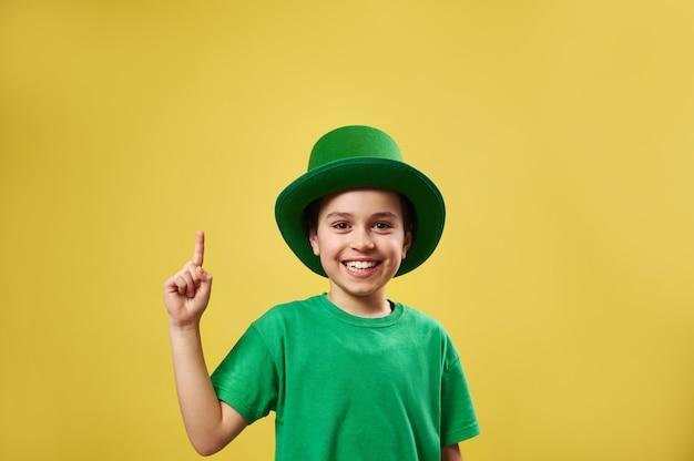 Menino engraçado com chapéu de duende irlandês apontando o dedo indicador para cima