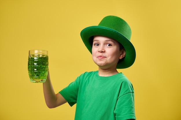 Menino engraçado com chapéu irlandês de duende verde com um copo de bebida verde comemorando o dia de são patrício