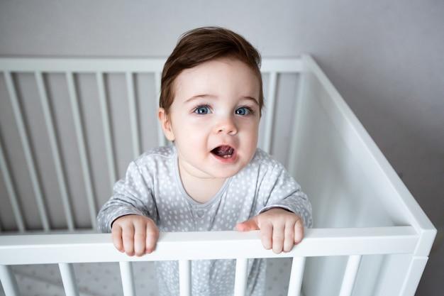 Menino engraçado com lindos olhos azuis em um berço branco