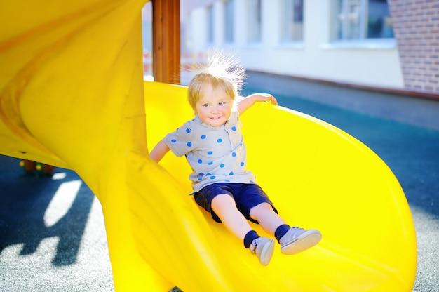 Menino engraçado da criança se divertindo no slide no playground