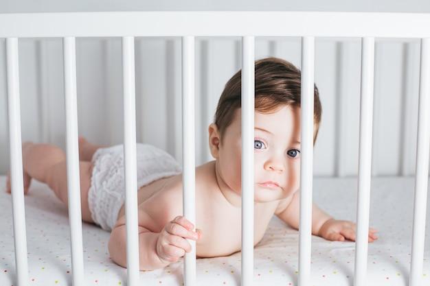 Menino engraçado deitado na cama de bebê e rindo