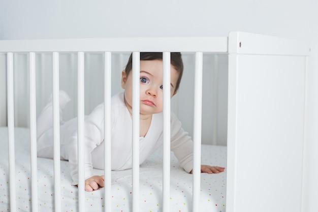 Menino engraçado deitado na cama de bebê