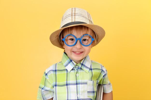 Menino engraçado e feliz de óculos e chapéu sorrindo