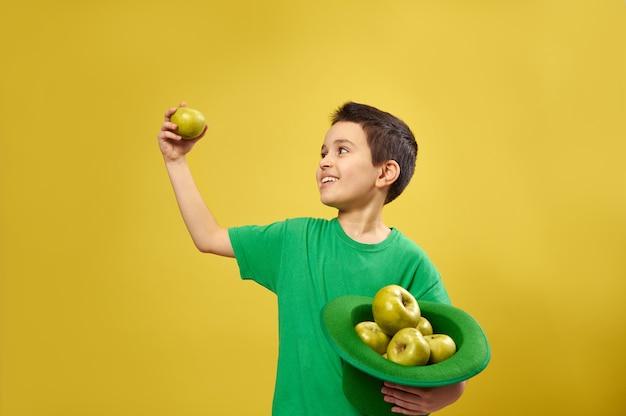Menino engraçado em pé na superfície amarela, segurando um boné verde irlandês cheio de maçãs em uma das mãos e olhando para uma maçã verde na outra
