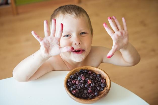 Menino engraçado mostra as mãos sujas depois de comer bagas