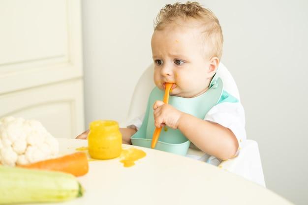Menino engraçado no babador comendo purê de vegetais com colher, sentado na cadeira infantil, aprende a comer ...