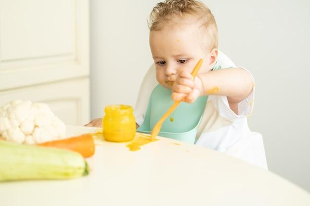 Menino engraçado no babador comendo purê de vegetais com uma colher, sentado na cadeira de criança. a criança aprende a comer sozinha.