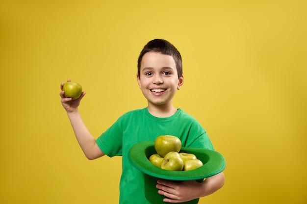 Menino engraçado parado isolado na superfície amarela e segurando um chapéu de duende irlandês cheio de maçãs em uma das mãos e uma maçã verde na outra