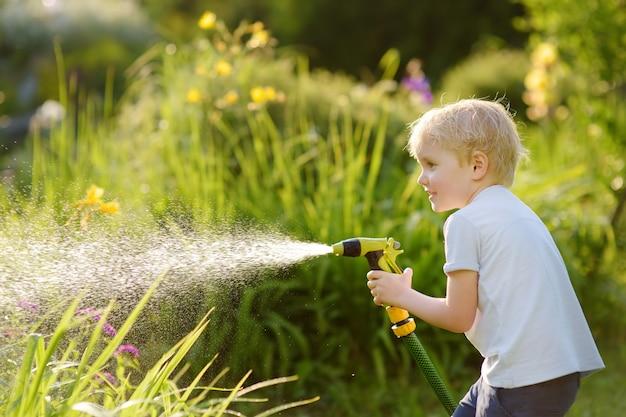 Menino engraçado que joga com mangueira de jardim no quintal ensolarado