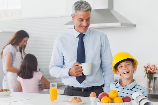 Menino engraçado que veste o capacete dos pais durante o café da manhã