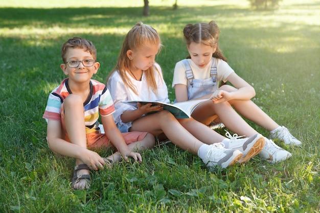 Menino engraçado sorrindo para a frente sentado na grama com seus amigos