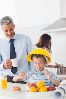 Menino engraçado vestindo capacete durante o café da manhã com seus pais