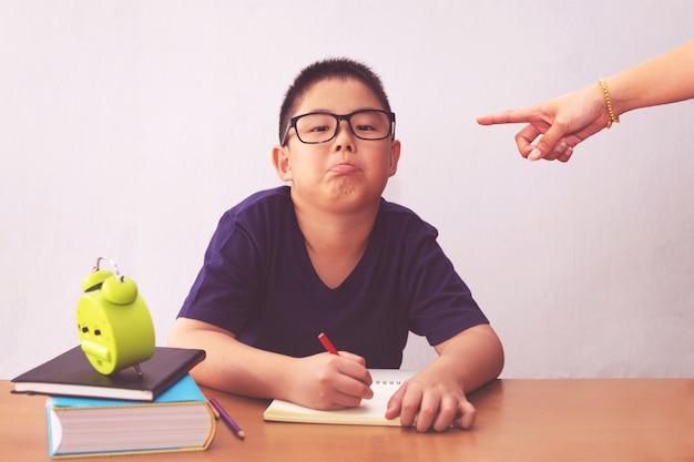 Menino entediado e cansado estudante asiática fazendo lição de casa. mãe irritada, apontando com ele