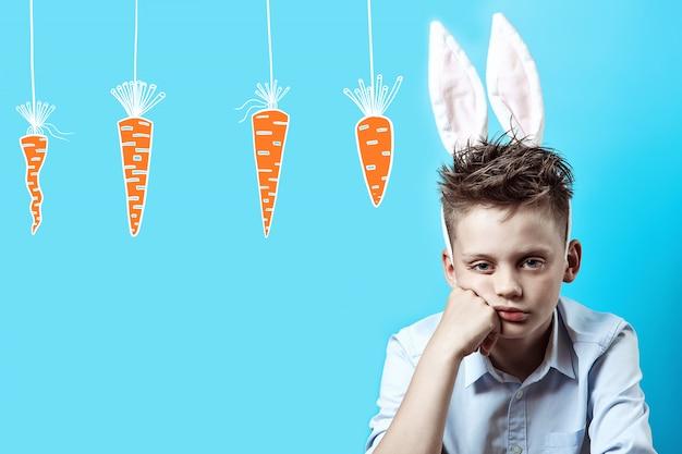 Menino entediado em uma camisa clara e orelhas de coelho em um azul