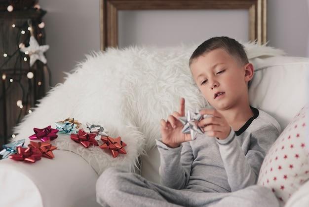 Menino entediado sentado em uma poltrona no natal