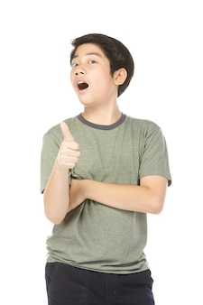 Menino entusiasmado asiático na camisa verde que dá o thumbs-up.