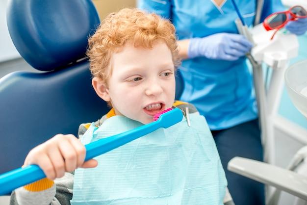 Menino escovando os dentes com uma escova grande, sentado na cadeira do consultório odontológico