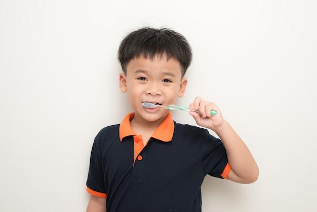 Menino escovando os dentes no fundo branco