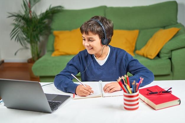 Menino escrevendo em um caderno e olhando para a tela de um laptop, dando aulas online, em casa, em ambientes fechados, em um espaço livre