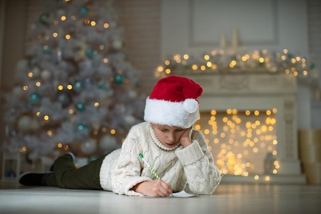 Menino escrevendo uma lista de desejos no chão com uma decoração de natal no fundo