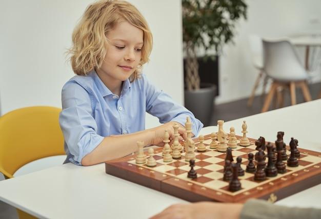 Menino esperto de camisa azul sentado na sala de aula olhando para o tabuleiro de xadrez enquanto joga