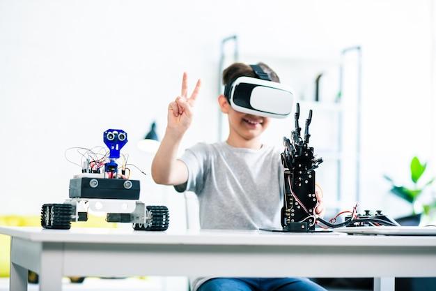 Menino esperto e alegre sentado à mesa testando sua criação robótica por meio de tecnologias de rv