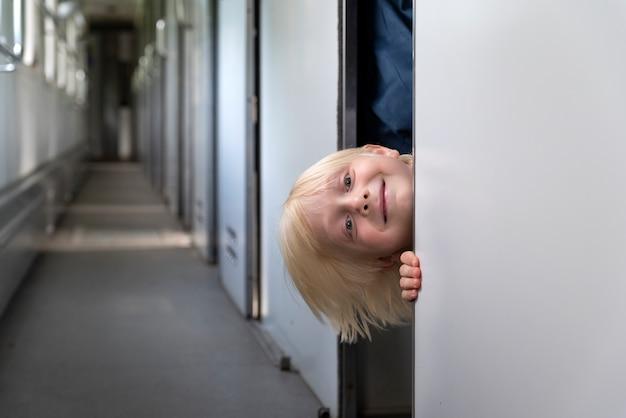 Menino espiando fora do vagão do compartimento