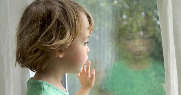 Menino está de pé e olhando pela janela