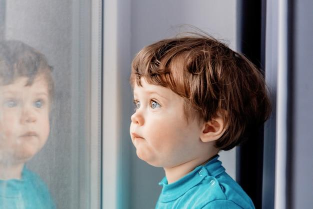 Menino está de pé junto à janela e olhando para ele