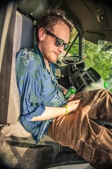 Menino está descansando em um assento de van enquanto bebe uma cerveja