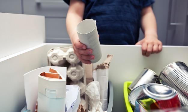 Menino está jogando lixo de papel em uma das quatro lixeiras diferentes para classificar o lixo.
