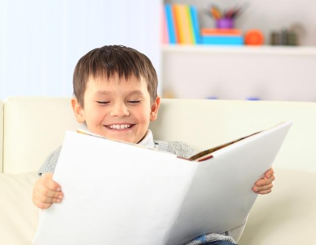 Menino está lendo um livro em casa