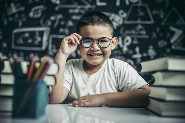 Menino estudando e segurando a perna de óculos em sala de aula.