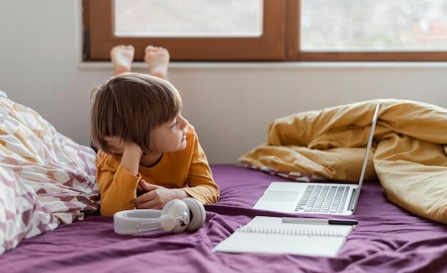 Menino estudando em casa e seu laptop