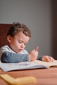 Menino estudando em casa enquanto pinta seu livro de imagens
