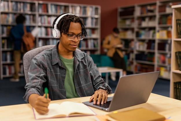 Menino estudando na biblioteca da universidade
