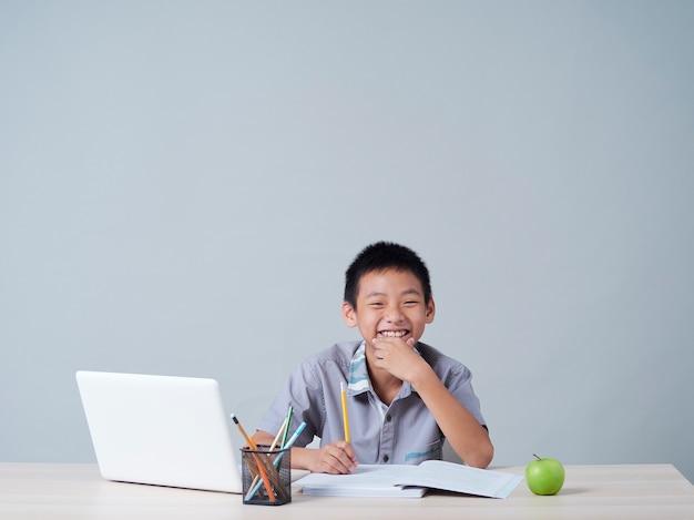 Menino estudando online com o laptop. aprendizagem à distância durante a pandemia covid-19